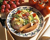 Colourful potato salad with frankfurters