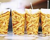 Four cardboard beakers of chips