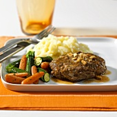 Hamburger steak with mashed potato and vegetables