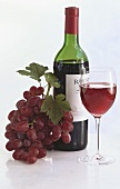 A bottle of red wine with glass of wine & grapes