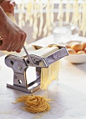 Running pasta dough through a pasta maker