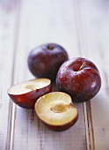 Two whole plums and one halved plum
