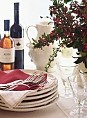 Table with pile of plates, cutlery and wine