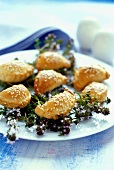Several pierogi (small pasties) and thyme on a plate