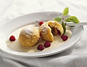 Plum dumplings with almond sauce and raspberries