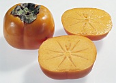 One whole and one halved sharon fruit