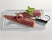 Two catfish fillets with knife on a board