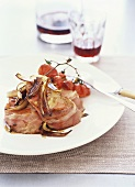 Veal wrapped in bacon with roasted cherry tomatoes