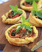 Mini puff pastry pizzas with tomatoes and mint
