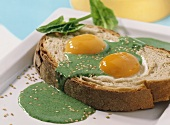 Slice of bread with fried eggs & spinach sauce