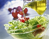 Pouring oil over salad leaves