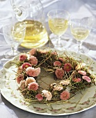 Heart-shaped wreath of Bellis and hay