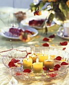 Bowl of water with candles and rose petals