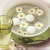 Marguerites and floating candles in a bowl