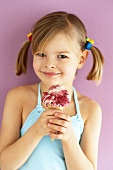 Small girl holding Amarena cherry ice cream with both hands