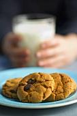 Kekse mit Schokoflocken, im Hintergrund Kind mit Milchglas