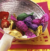 Sweets in coloured wrappers in a dish