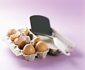Three whole eggs and eggshells in an egg box