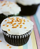 Chocolate muffin with icing and orange sprinkles