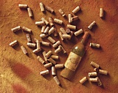 A Bordeaux bottle and corks in sand
