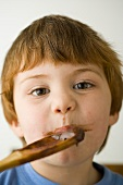 Small boy licking a wooden spoon