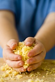 Child's hands holding grated cheese