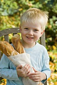 Blond boy holding two baguette sticks in paper