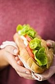 Zwei Hände halten ein Sandwich mit Hähnchenbrust