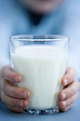 Child's hands holding a glass of milk