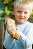 Blond boy holding a baguette stick