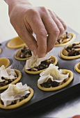 Putting filo pastry on top of mincemeat tarts