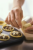 Putting pieces of marzipan on top of mincemeat tarts