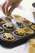 Putting pastry stars on top of mincemeat tarts