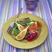 Ham and figs on salad leaves