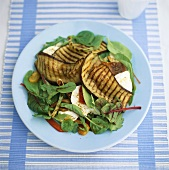 Grilled aubergine slices on mixed salad leaves
