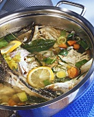 Fish stock with ingredients in pan