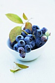 Blueberries with leaves in a small bowl
