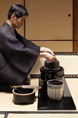 Tea master at tea ceremony, putting kettle on