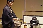Tea master at tea ceremony, cleaning utensils