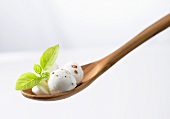 Mozzarella balls and basil on a wooden spoon