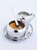 Brown sugar in a sugar bowl with milk jug