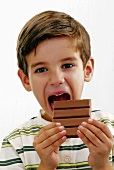 Small boy biting into a bar of chocolate