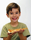 Small boy holding a piece of pizza in his hands