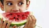 Small boy biting a slice of watermelon