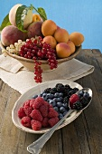 Bowl of mixed fruit and plate of berries