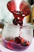 Ladling berry jam into a jar