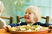 Laughing boy, nachos with tomato salsa and guacamole