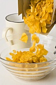 Tipping cornflakes into a bowl