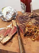 T-bone steak with baked potatoes and fried onions
