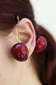Pair of cherries hanging on a model's ear